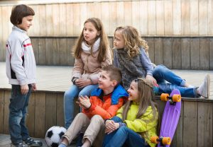 Group of children portrait with ball and skateboard outdoors